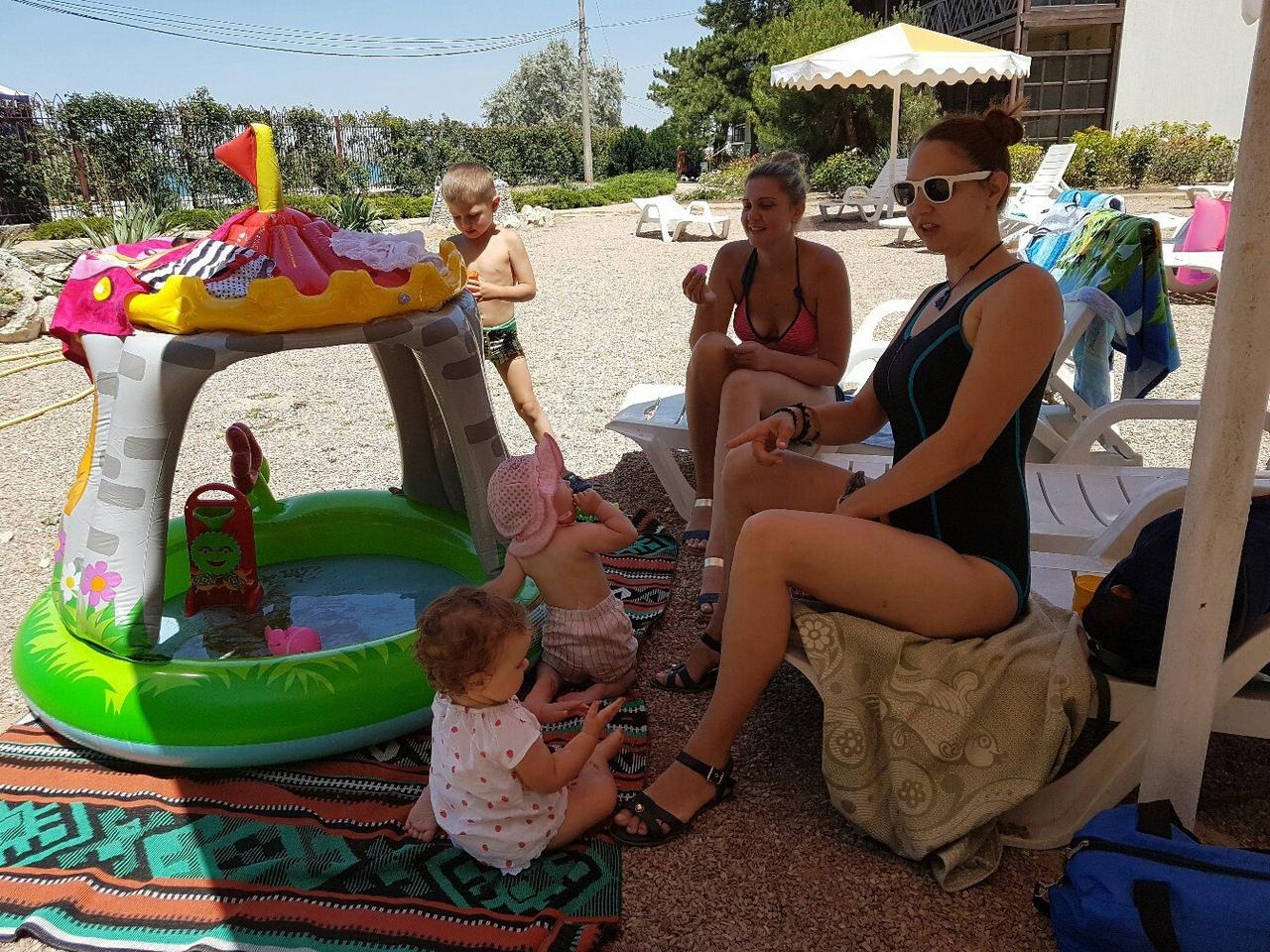 Обратите внимание бассейн-плескалка стоит на прочном паласе. Мамы и дети в тени.